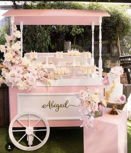 pink candy cart with sweets and balloons
