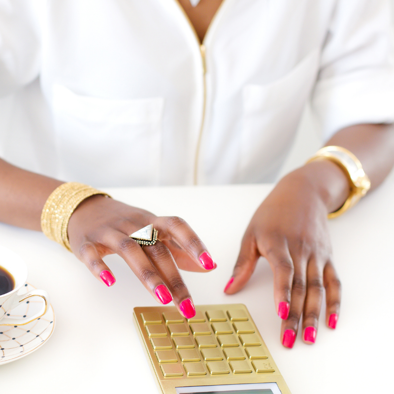 business woman using calcultaor in gold